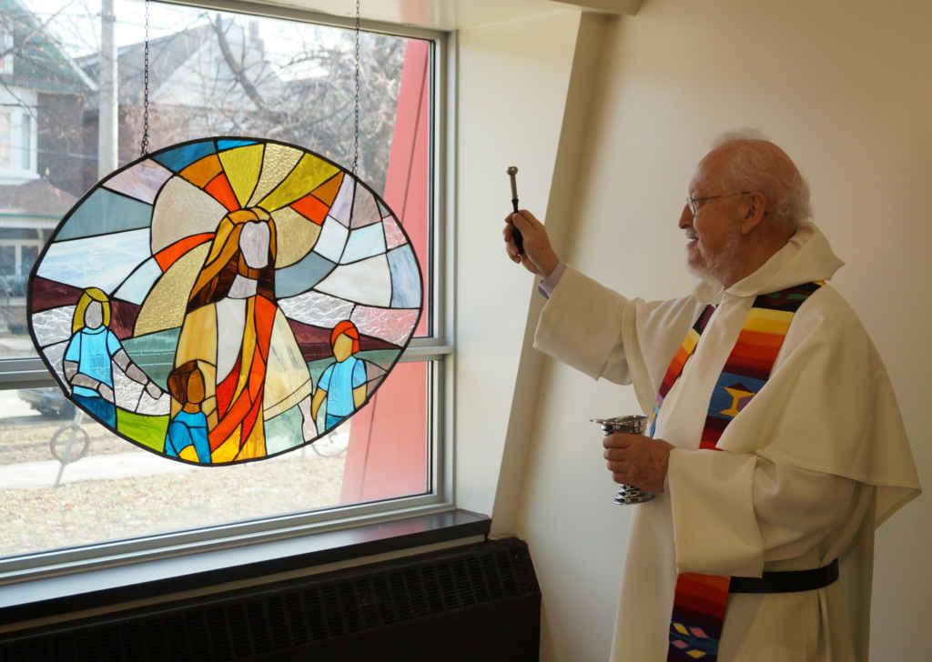 Le père Michel Côté, o.p., résident à la paroisse Sacré-Cœur, bénit les vitraux.