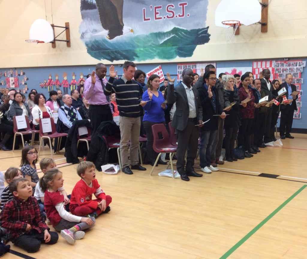 Les 20 nouveaux citoyens canadiens prêtent serment.