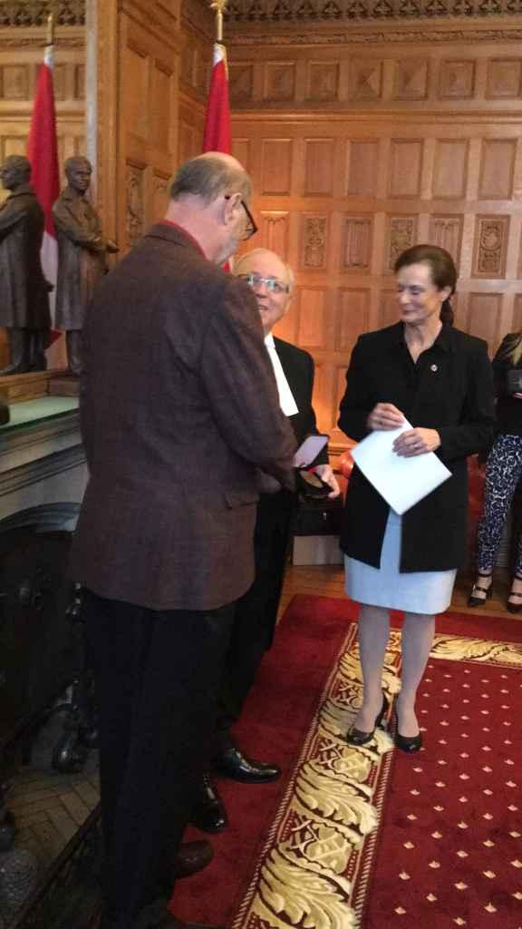 Paul-François Sylvestre recevant sa médaille du 150e du président du Sénat, George Furey, en présence de la sénatrice Lucie Moncion.