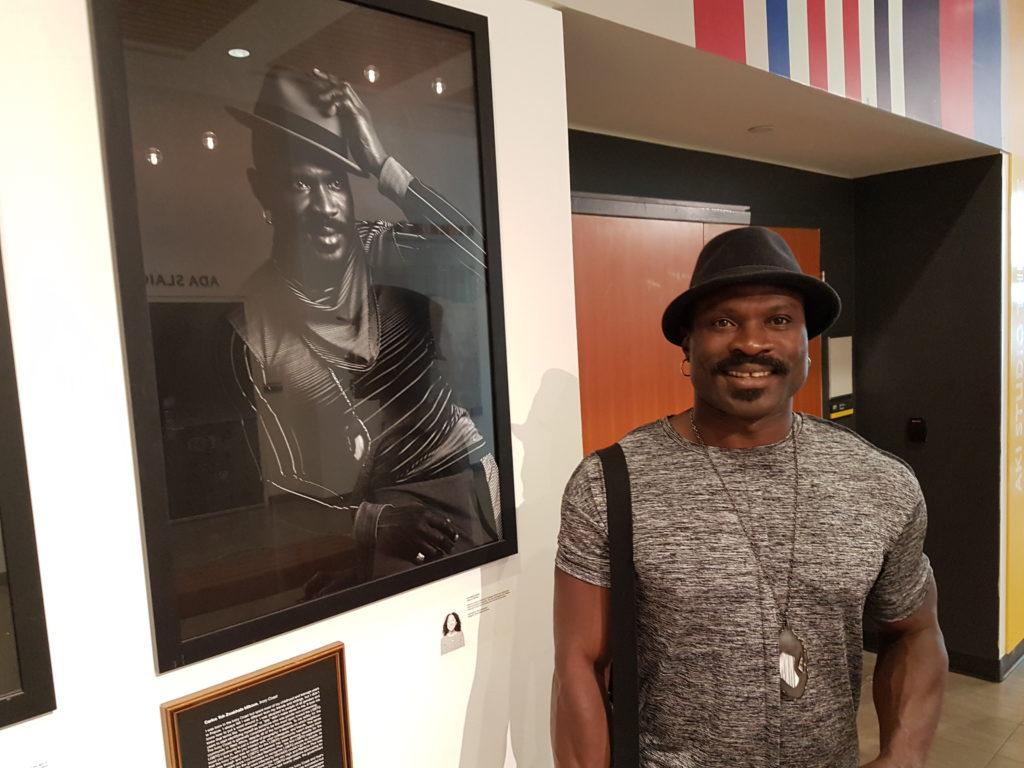Photo de Carlos Idibouo devant son portrait