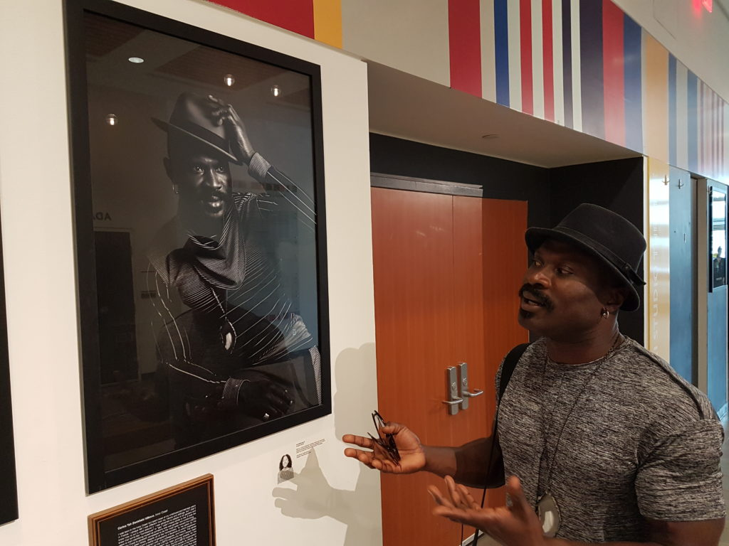 Photo de Carlos Idibouo qui parle devant son portrait